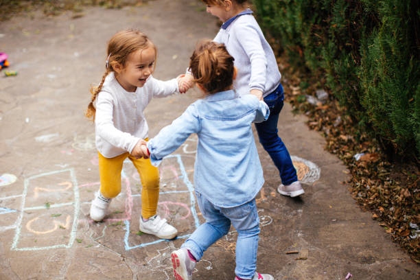 Toddler friends playing hopscotch outdoors stock photo