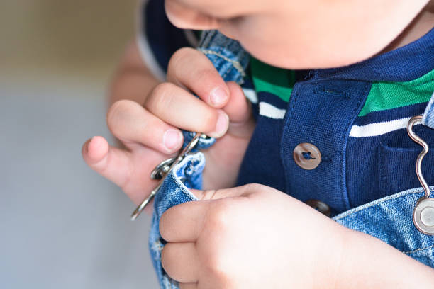 Toddler Getting Dressed An independent toddler boy, trying to dress himself in overalls, clips the last strap onto his overalls. bib overalls boy stock pictures, royalty-free photos & images
