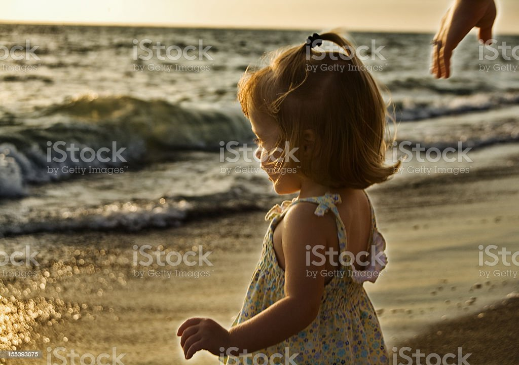 Toddler girl at the beach stock photo