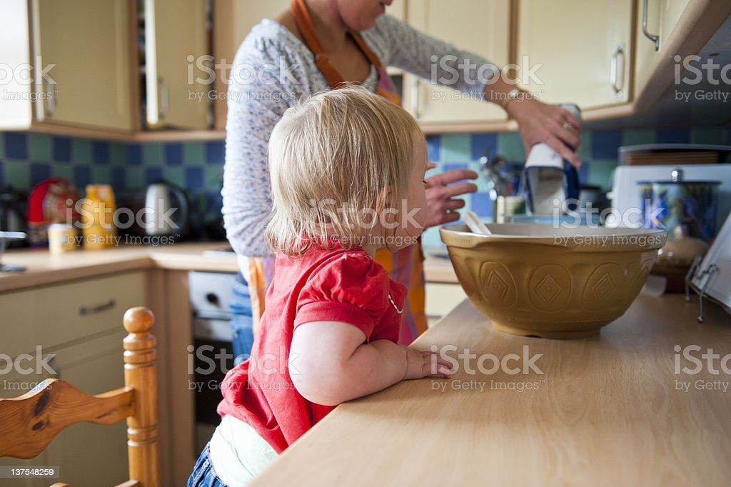 Toddler girl baking with mother stock photo