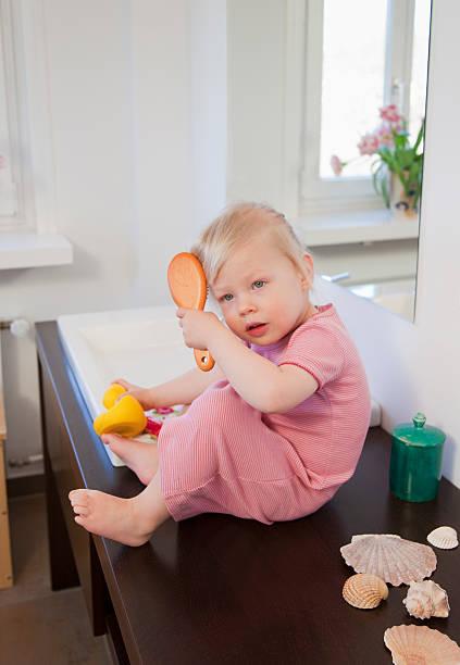 Toddler girl brushing her hair stock photo