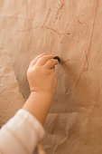 Toddler Girl Coloring a Piece of Kraft Paper with a Brown Crayon.
