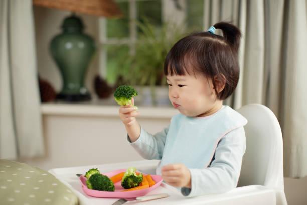 kleinkind mädchen essen gesundes gemüse sitzen auf hohen stuhl neben einem esstisch zu hause - füttern stock-fotos und bilder