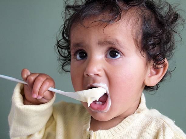 Kleinkinder – Mädchen Fütterung selbst mit einem Löffel der Haferbrei. – Foto