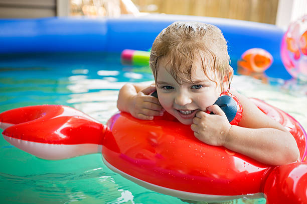 Toddler girl floating on pool toy stock photo
