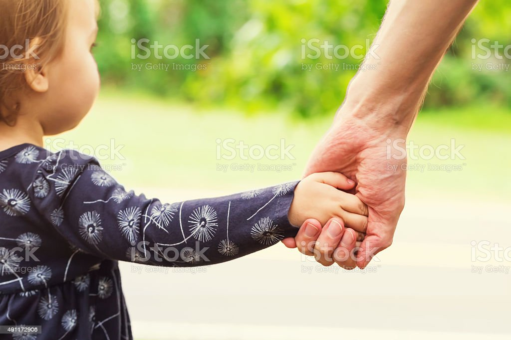 Toddler girl holding hands with her father stock photo