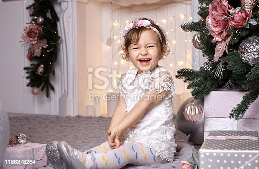 892959344 istock photo Toddler girl in a white dress laughs joyfully on a background of Christmas illumination 1186378264