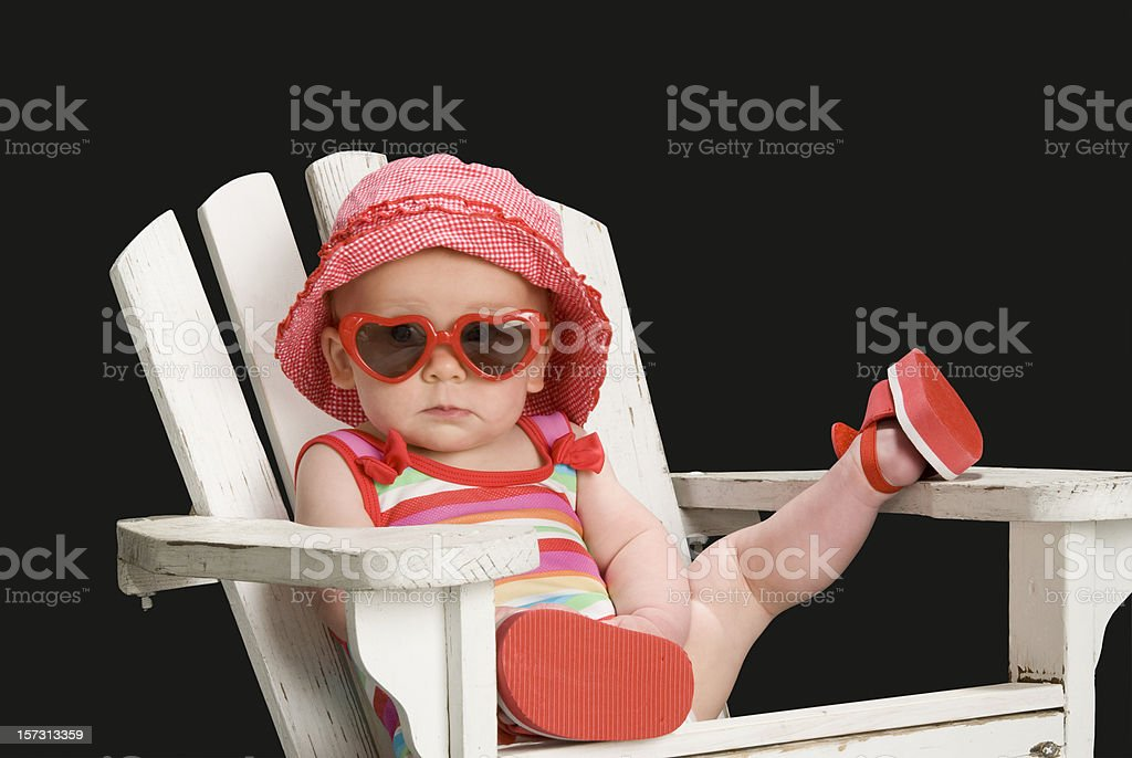 Toddler girl in Adirondack chair w/leg up,sunglasses on-total relaxation stock photo