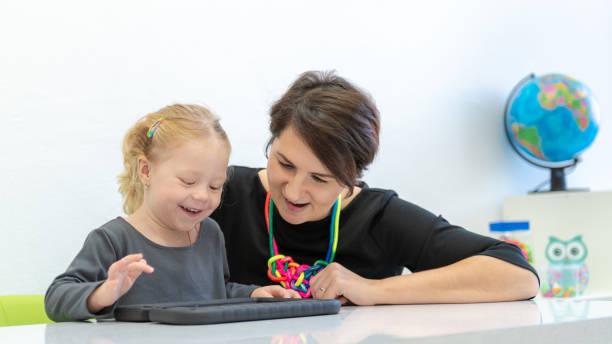 Kleinkind Mädchen in Kinder-Ergotherapie-Sitzung machen spielerische Übungen auf einem digitalen Tablet mit ihrem Therapeuten. – Foto