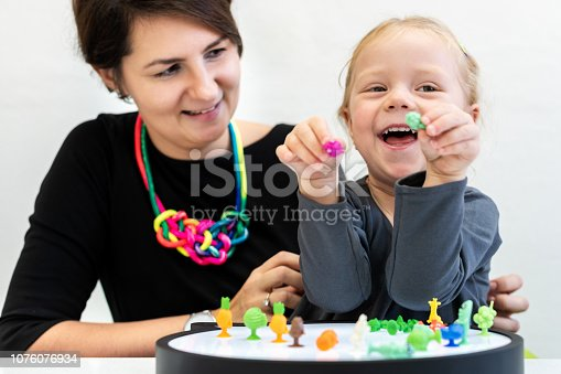 istock Toddler girl in child occupational therapy session doing sensory playful exercises with her therapist. 1076076934
