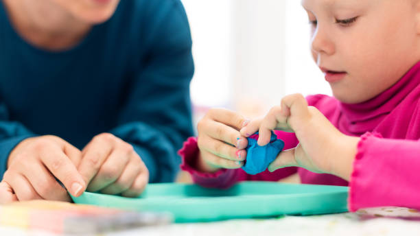 Kleinkind Mädchen Kind Ergotherapie Sitzung sensorische spielerische Übungen mit ihrem Therapeuten. – Foto