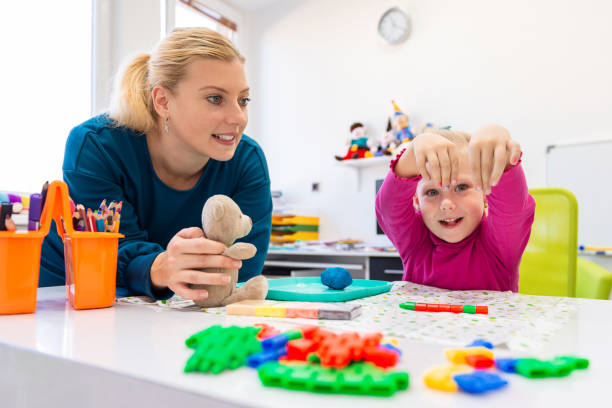 toddler girl in child occupational therapy session doing sensory playful exercises with her therapist. - sensory perception stock pictures, royalty-free photos & images