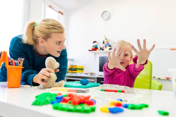 Kleinkind Mädchen in Kinder-Ergotherapie-Sitzung machen sensorische spielerische Übungen mit ihrem Therapeuten. – Foto