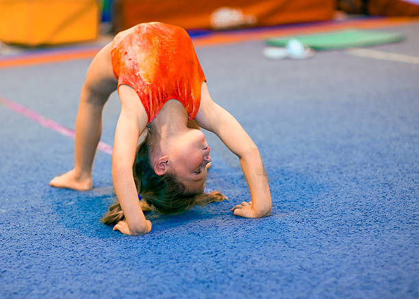Toddler girl in leotard doing a bridge Children can excel at gymnastics, even beginning at a very young age! This toddler girl, aged 4, is demonstrating a Bridge position by pushing off her hands and feet and thrusting her back upwards. She is looking right. bending over backwards stock pictures, royalty-free photos & images