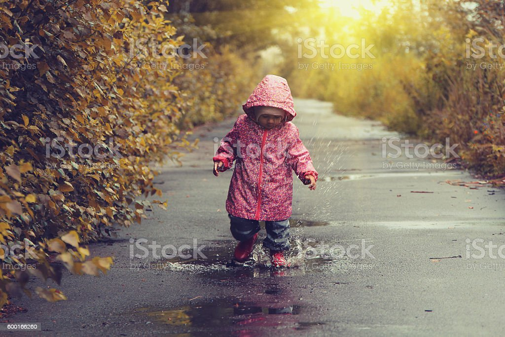 Toddler girl jumping in puddles after rain - foto de acervo