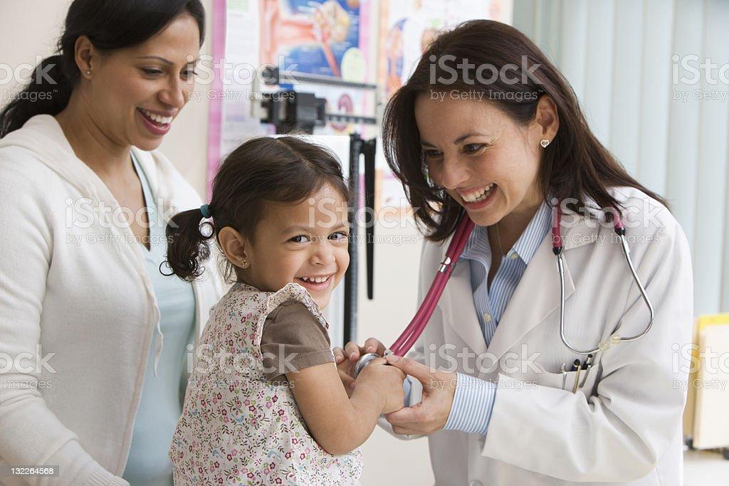 Menina bebê rindo enquanto médico examina - foto de acervo