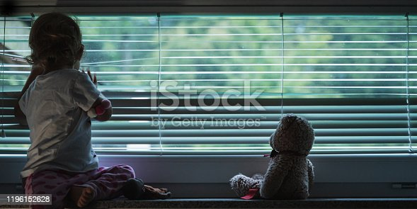 Toddler girl looking out the window through lowered venetian blinds with her teddy bear sitting next to her in a conceptual image.