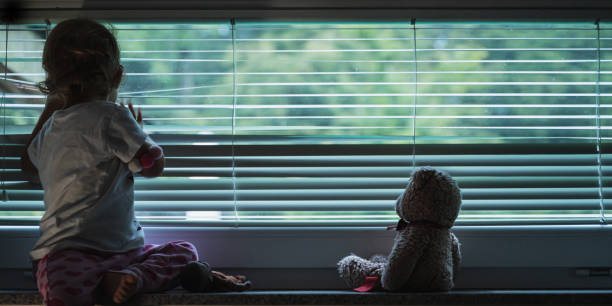 Toddler girl looking out the window stock photo