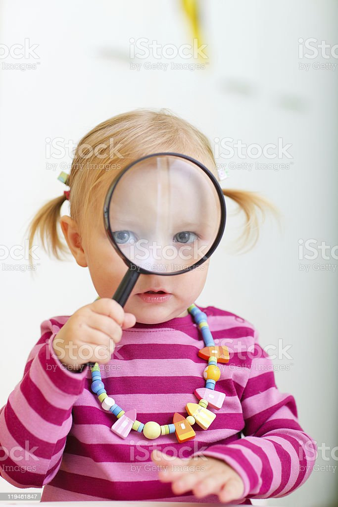 Toddler girl looking through magnifier royalty-free stock photo