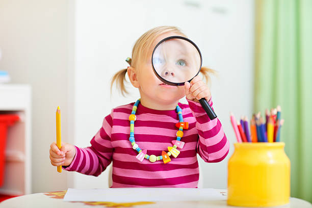 Toddler girl looking through magnifier stock photo