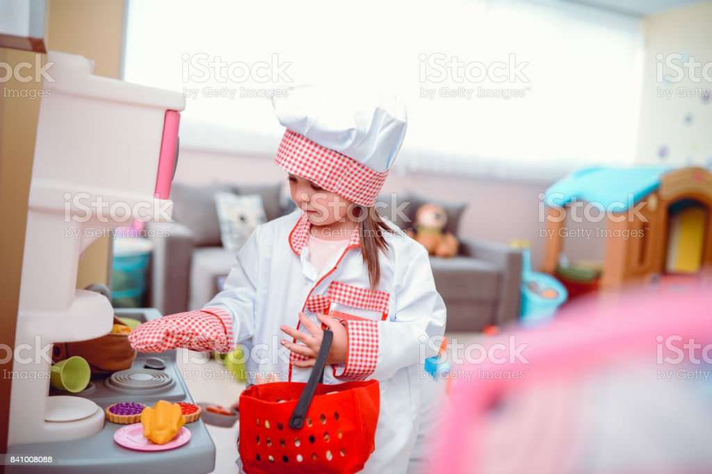 Toddler Girl Playing Cooking Chef in a Preschool Classroom stock photo