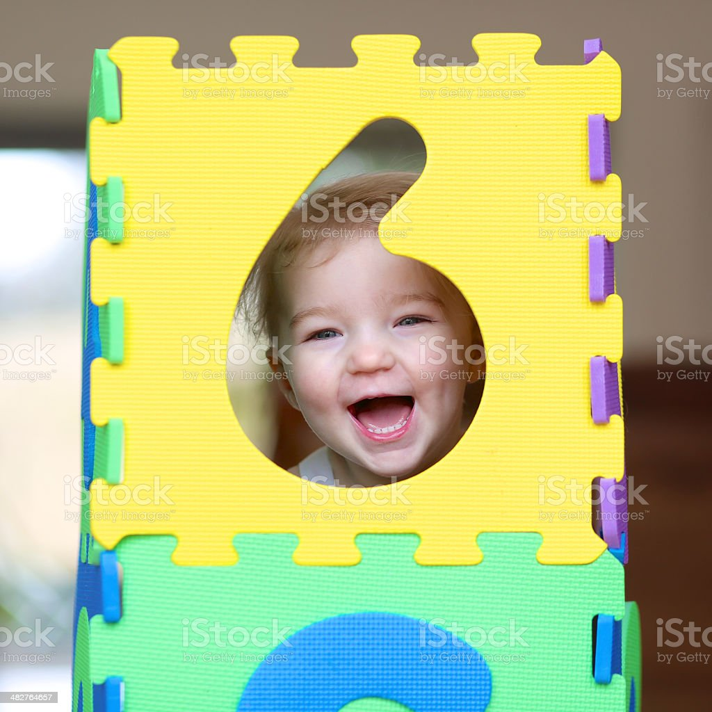 Toddler girl playing indoors with puzzles stock photo