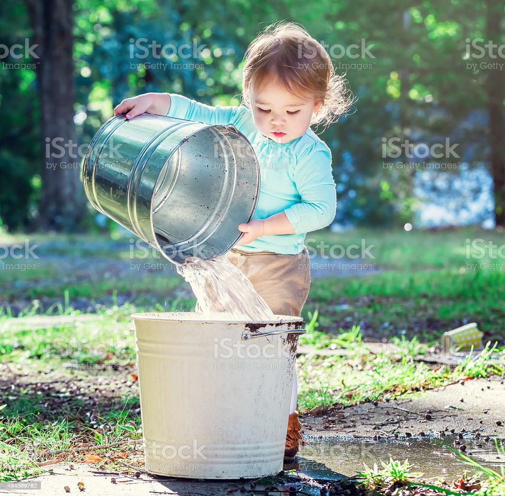 Toddler girl playing outside with buckets stock photo