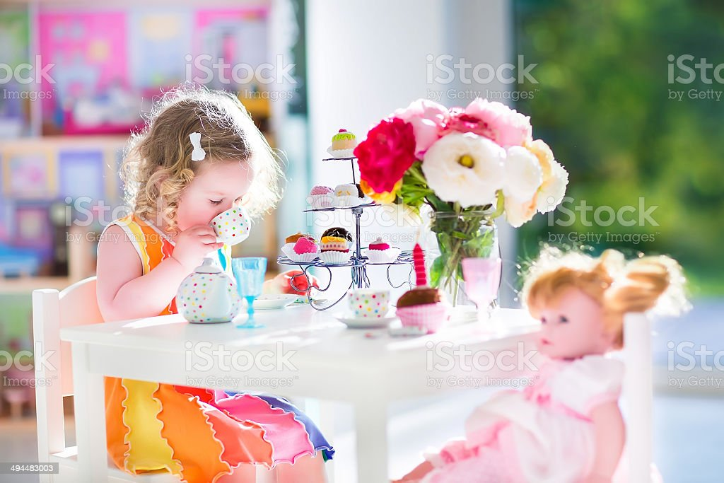 Toddler girl playing tea party with a doll stock photo