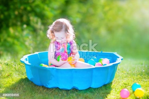 Happy cute toddler girl with curly hair wearing a pink colorful dress playing in a sand box with plastic toy balls in a sunny green garden on a hot summer day