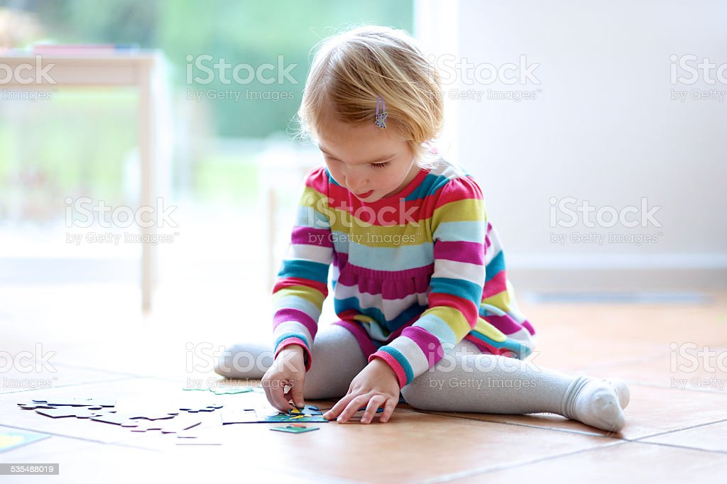 Toddler girl playing with jigsaw puzzles indoors stock photo