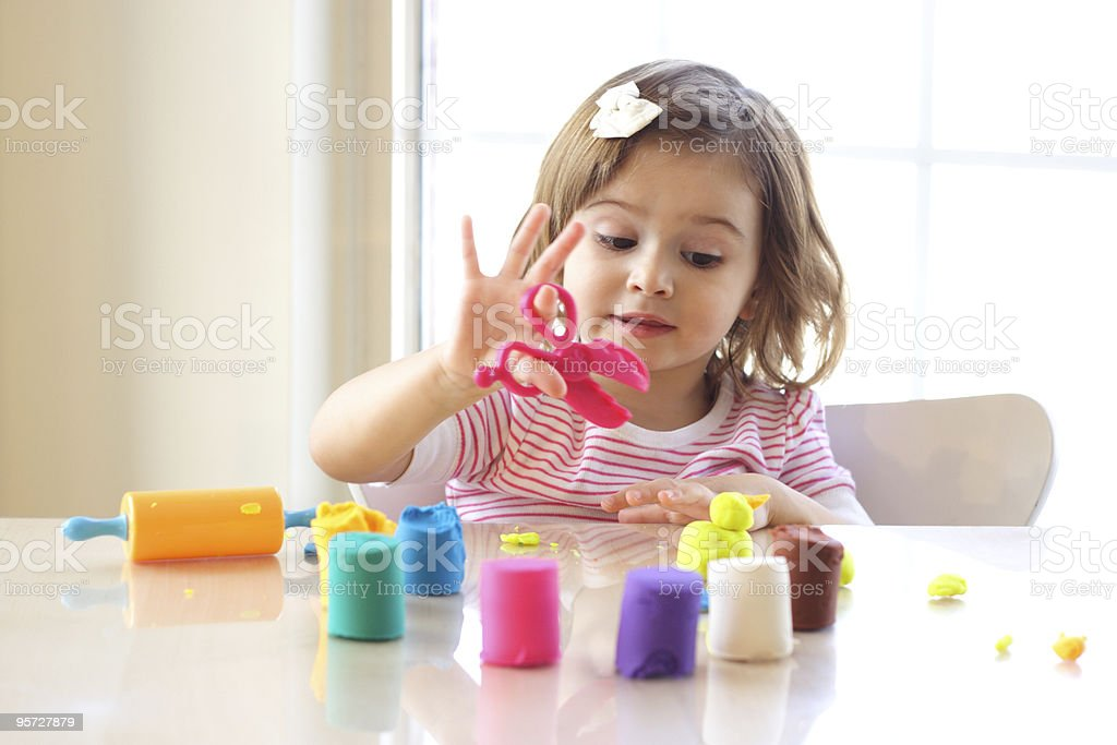 Toddler girl playing with playdough on kitchen counter stock photo