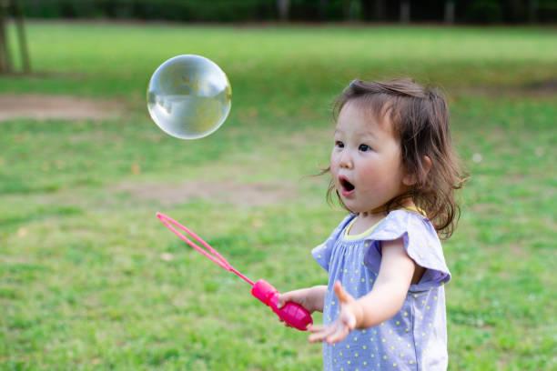 kleinkind mädchen spielt mit seifenblasen - toddler stock-fotos und bilder
