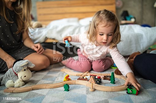 917360086 istock photo Toddler girl playing with wooden train on floor 1183099734