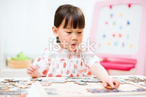 514261930 istock photo toddler girl playing wooden puzzle at home 1224891475