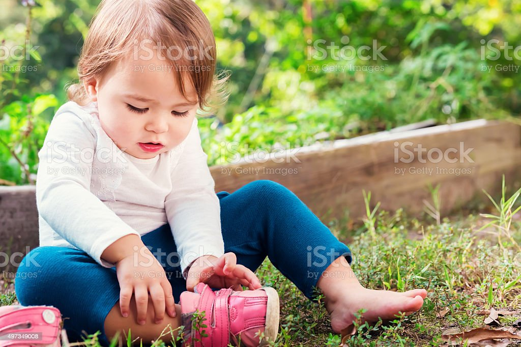 Toddler girl putting on her sneakers stock photo