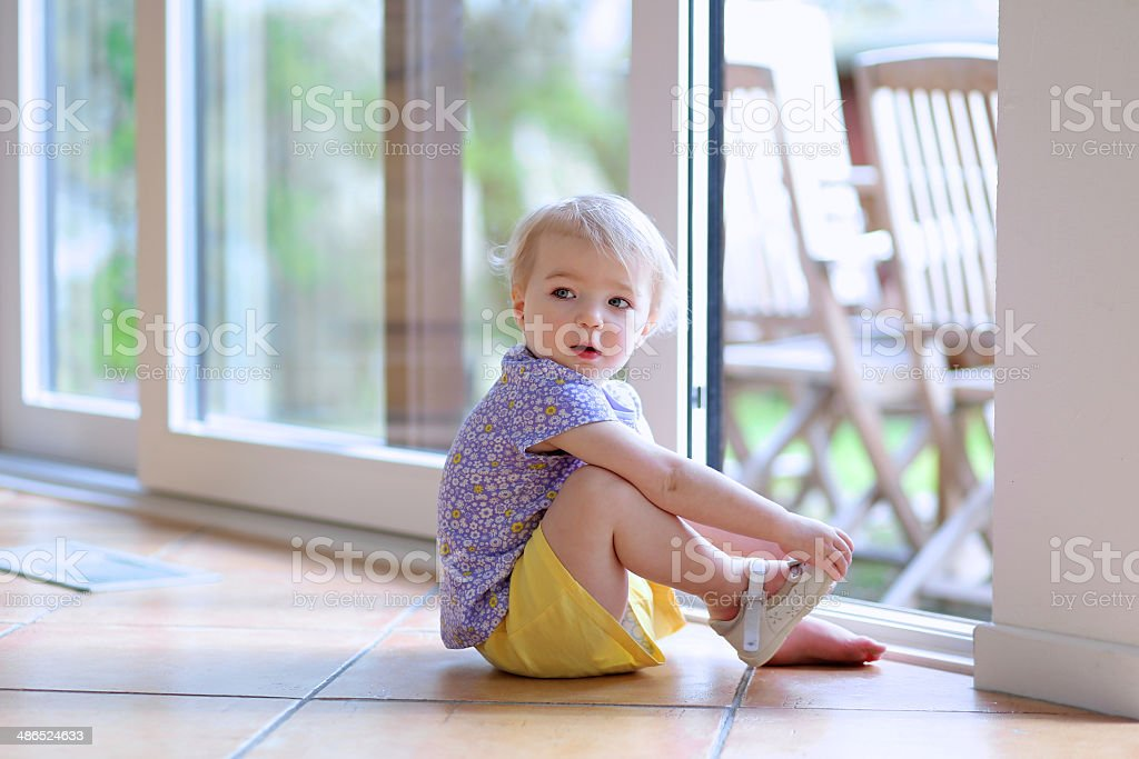 Toddler girl putting shoes sitting on floor next to window stock photo