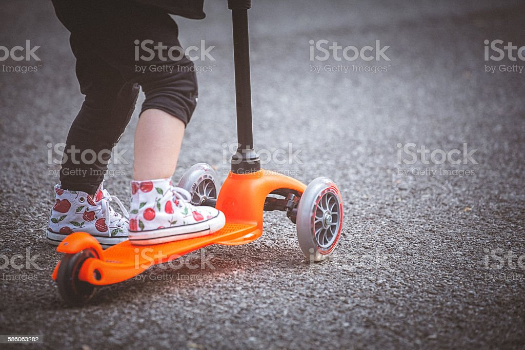 Toddler girl riding push scooter on pavement. stock photo