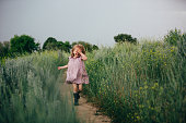 3 year old with long blonde hair, wearing a purple dress in a field of tall high green grass. Holding her hand over her face.