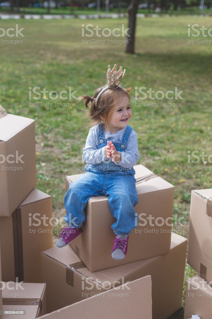 Toddler girl sitting on carboard boxes foto de stock royalty-free