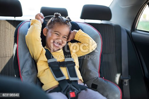 istock Toddler girl sitting on safety car chair. 623195540