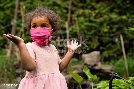 Beautiful toddler girl smiling behind her stylish protective pink mask. She his mixed-race and is wearing a pink dress. Nature in background. Horizontal outdoors waist up shot with copy space.