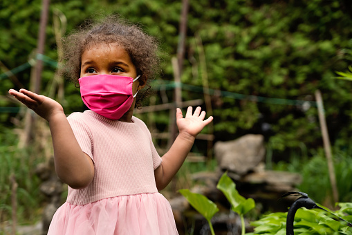 Toddler girl smiling behing stylish protective mask.