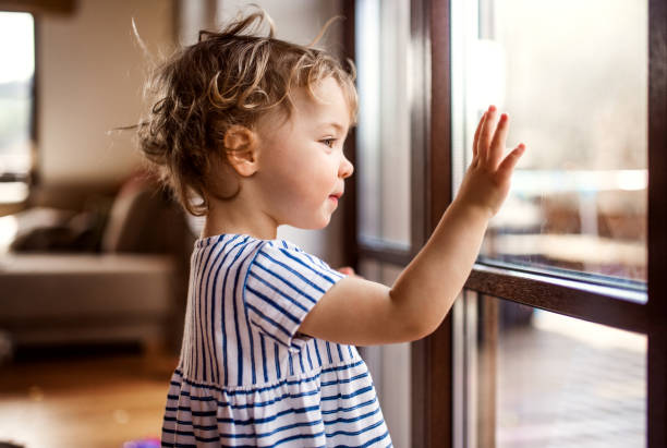 a toddler girl standing by window indoors at home, looking out. - sventolare la mano foto e immagini stock
