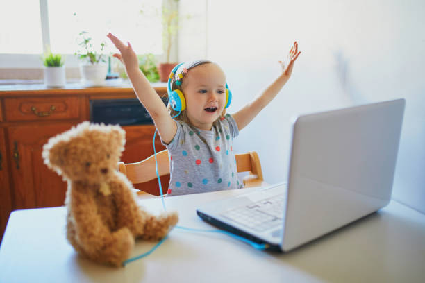 Toddler girl wearing eraphones with laptop stock photo