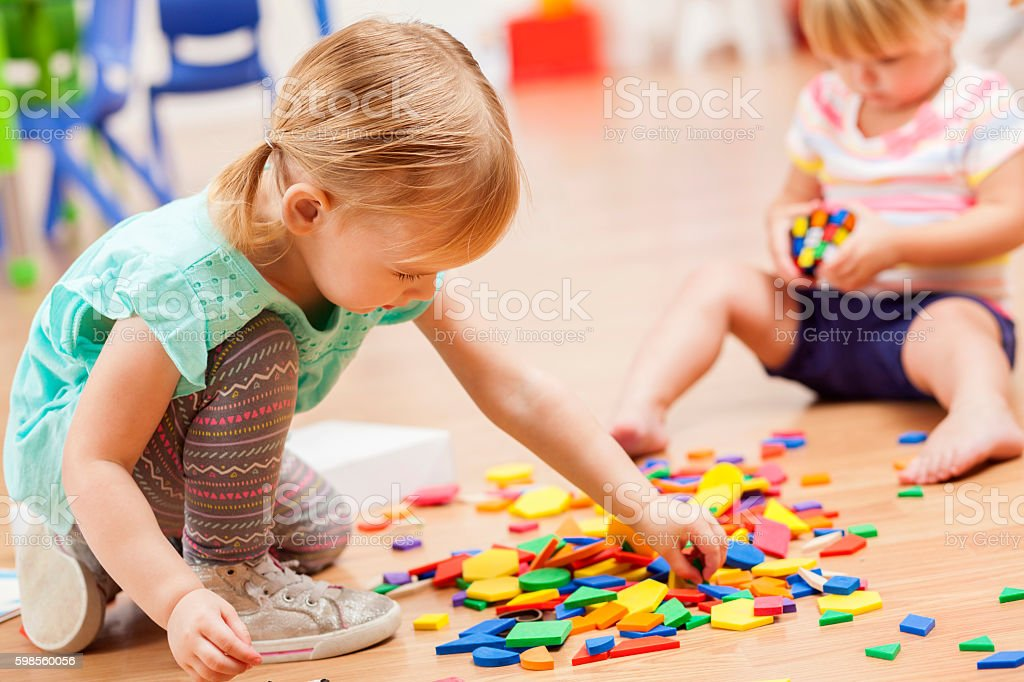 Toddler girls playing with puzzle pieces in a preschool classroom stock photo