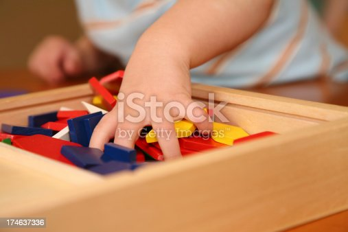 istock Toddler Grabbing a Handful of Toy Blocks 174637336