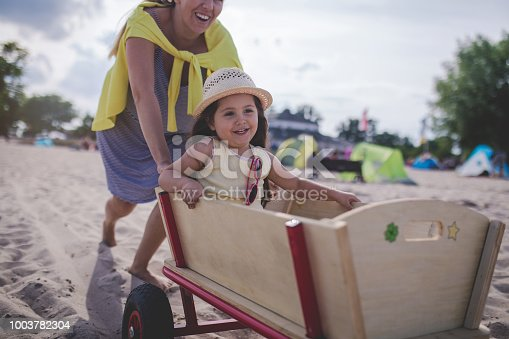 Lovely and cute child with a hat, sitting in a trolley on the beach, enjoying the ride.