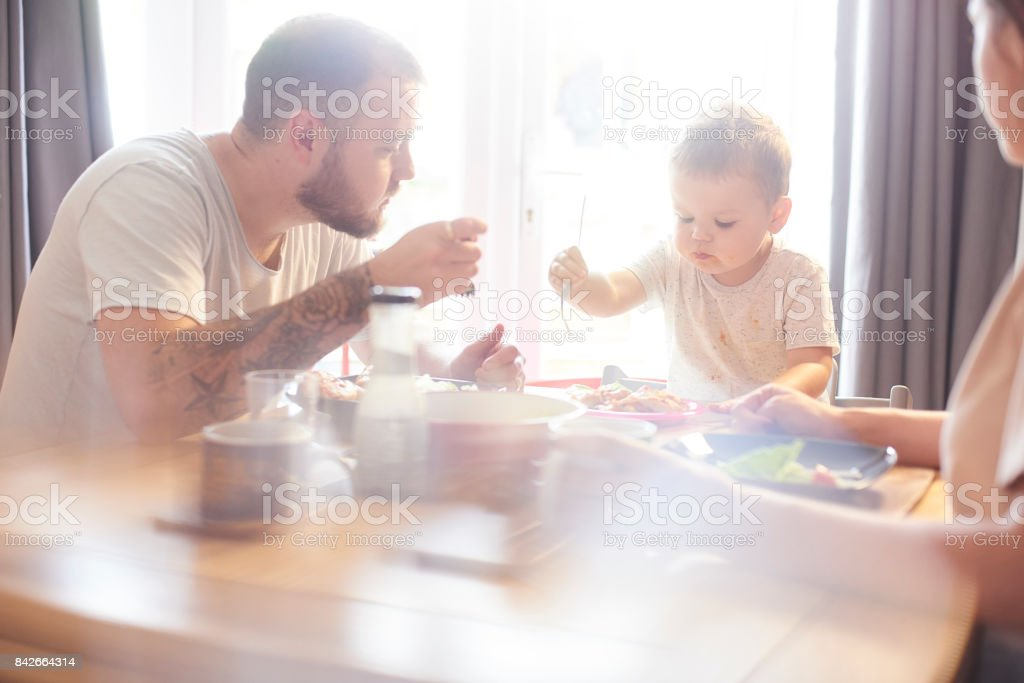 Toddler having his lunch with mummy and daddy stock photo