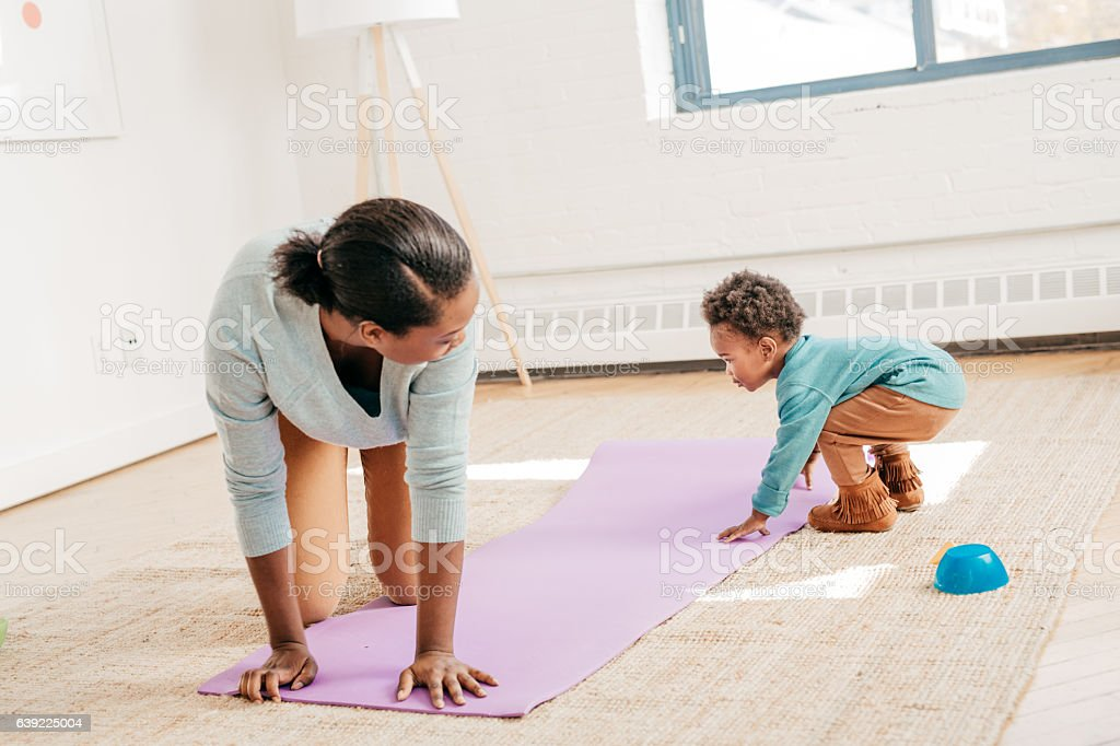 Toddler helps with yoga pad stock photo