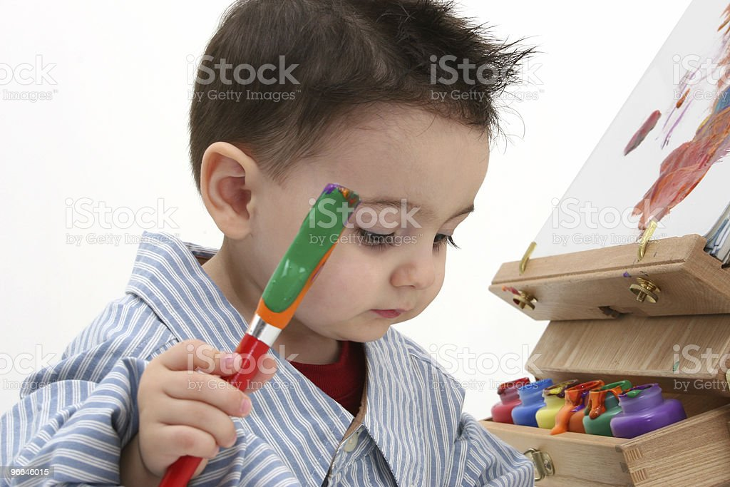 A toddler holding a paintbrush in front of a canvas royalty-free stock photo